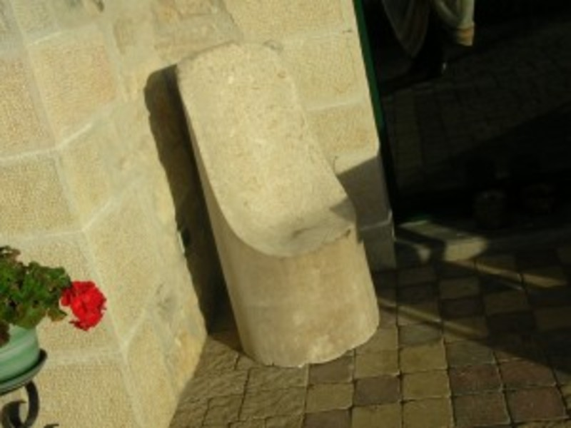 Chaise fauteuil en pierre dure, incluse dans un morceau de colonne, forme du siège très confortable. 2 escargots sculptés en pierre se rejoignent en haut du dossier