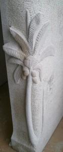 Sur le jambage en pierre, un cocotier sculpté
