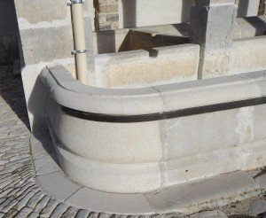 Détail d'une margelle arrondie et moulurée en pierre calcaire
