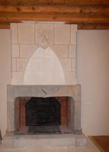 Habillage de la hotte de cheminée en pierre bouchardée, taille d'un arc en ogive. La clé de l'arc est orné d' un blason sculpté du lion de Franche-Comté.