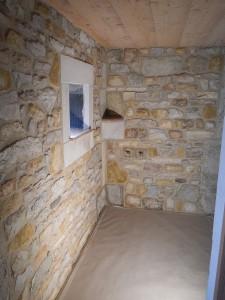 Habillage d'une salle de bain, en pierres à maçonner multicolores avec encadrement de fenêtre et tablette