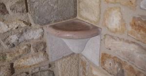 Détail de la tablette de salle de bain en pierre moulurée polie et bouchardée